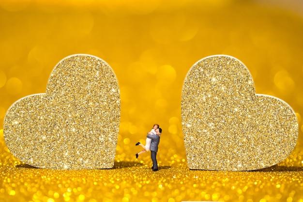 Miniaturmenschen und goldene herzen. ein liebendes paar auf einem strahlenden hintergrund.