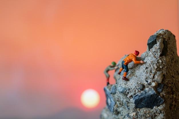 Miniaturmenschen: wanderer klettern auf den felsen. sport- und freizeitkonzept.