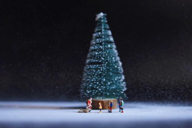 Miniaturmenschen weihnachtsmann mit leuten unter dem großen weihnachtsbaum.