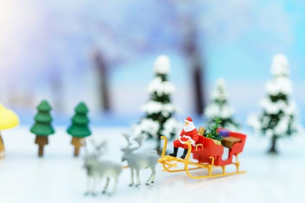 Miniaturmenschen: weihnachtsmann sitzend rentierschlitten mit gruß oder postkarte und weihnachtsbaum.