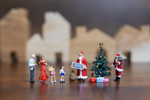 Miniaturmenschen: weihnachtsmann und glückliche familie