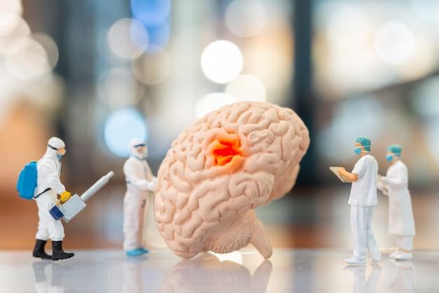 Miniaturmenschenarzt und -krankenschwester, die über das menschliche gehirn, die wissenschaft und das medizinische konzept beobachten und diskutieren