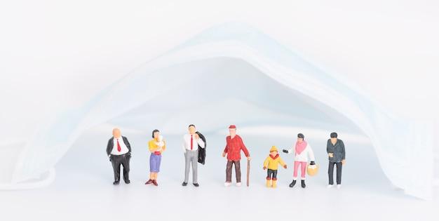 Miniaturmenschenfamilie mit chirurgischer maske auf weißem hintergrund, um vor der vorbeugung der coronavirus-krankheit zu schützen.