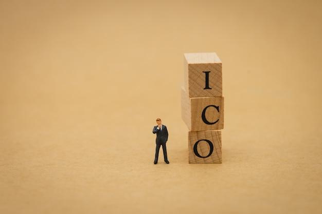 Miniaturmenschengeschäftsleute, die mit holzwort ico (anfängliches münzenangebot) stehen