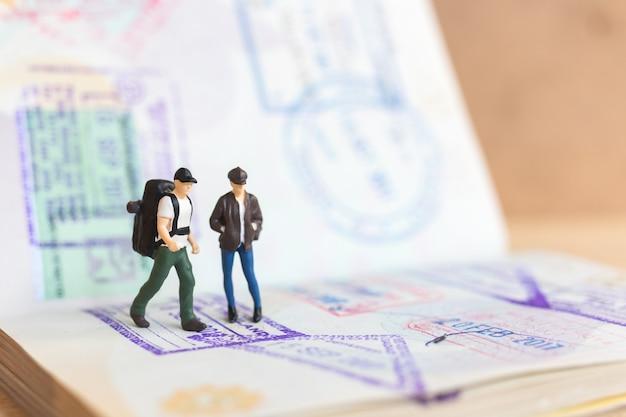 Miniaturmenschenpaar, das auf pass mit einwanderungsstempel steht, reisekonzept.