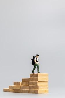 Miniaturmenschenreisender, der auf holzblock auf grauem hintergrund steht. reise- und abenteuerkonzept