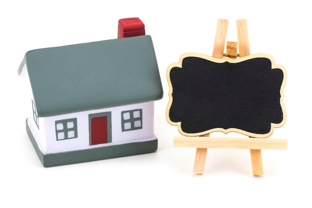 Miniaturmodell der hausimmobilie zur miete etikett auf weiß