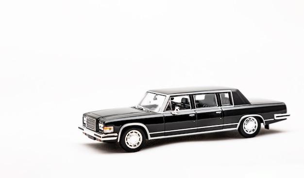 Miniaturmodell eines schwarzen retro-autospielzeugs isoliert auf weißem hintergrund