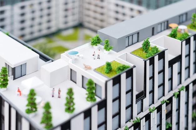 Miniaturmodell, miniaturspielzeuggebäude, autos und menschen. stadtmaquette. neues bauprojekt
