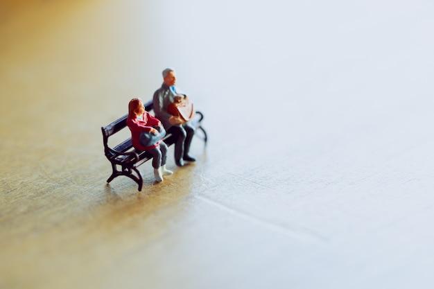 Miniaturpaare, die zusammen im warmen licht sitzen.