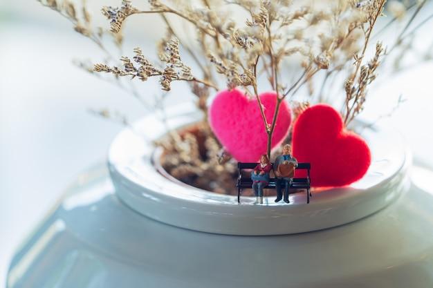 Miniaturpaare, die zusammen vor reizendem blumenhintergrund mit rotem herzen sitzen.