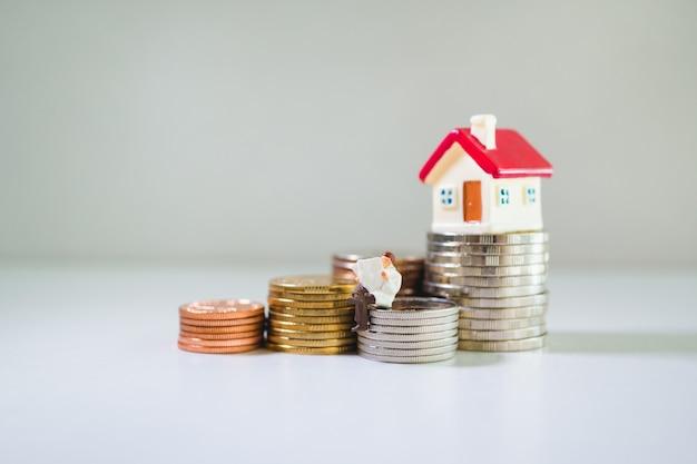 Miniaturpaare und haus auf münzenstapel