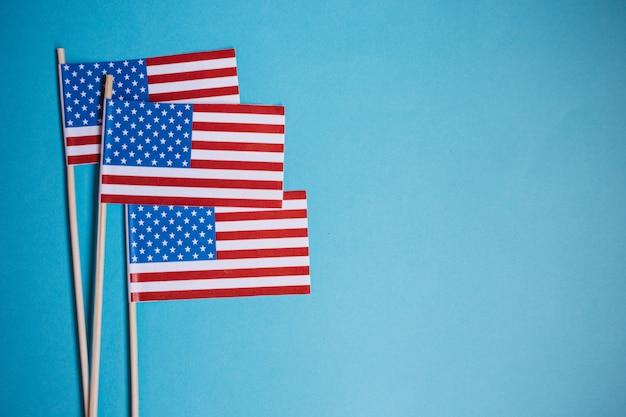 Miniaturpapierfahne usa. amerikanische flagge auf blauem hintergrund.