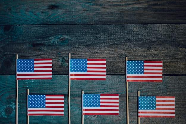 Miniaturpapierfahne usa. amerikanische flagge auf rustikalem hölzernem hintergrund.