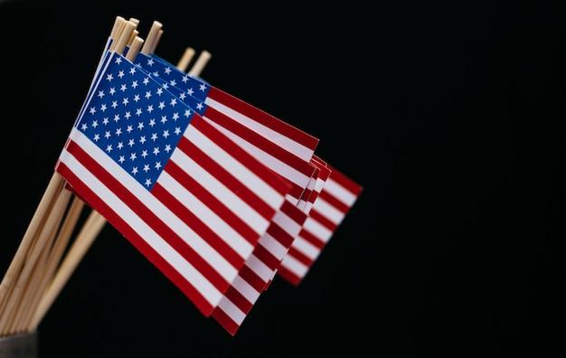 Miniaturpapierfahne usa. amerikanische flagge auf schwarzem hintergrund.