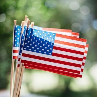 Miniaturpapierflaggen usa. amerikanische flagge auf unscharfem hintergrund draußen