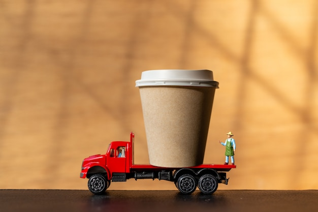Miniaturperson auf lkw und kaffeetasse zum mitnehmen