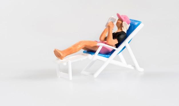 Miniaturperson, die auf einem deckchair sich entspannt