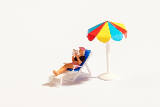 Miniaturperson, die ein buch unter einem regenschirm liest
