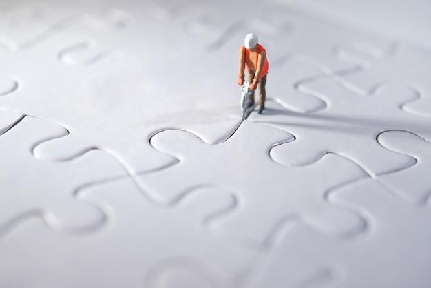 Miniaturperson, die puzzlespiele konstruiert, platz für das team und das arbeitskonzept macht. aufwand konzept