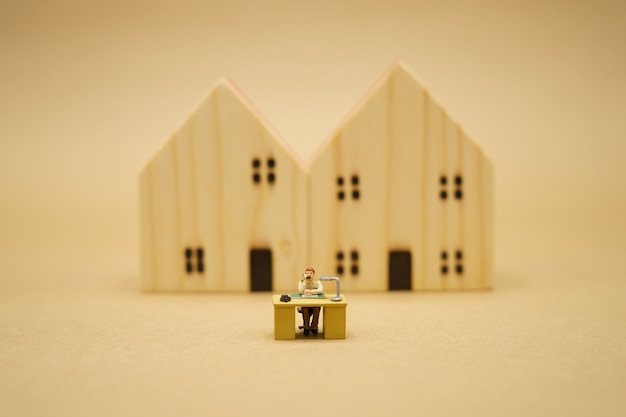 Miniaturperson, die von zu hause aus arbeitet