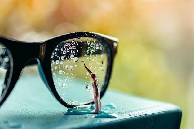 Miniaturreiniger wischen sie viele tröpfchen auf den brillen aus, um sie zu entfernen