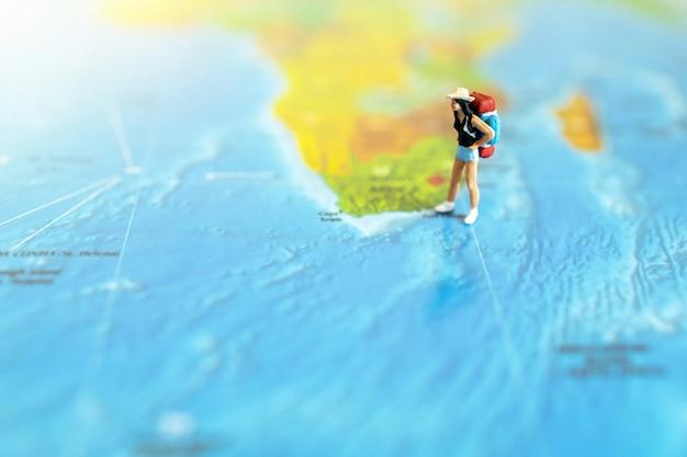 Miniaturreisender mit einem rucksack, der auf weltkarte steht. reisekonzept.