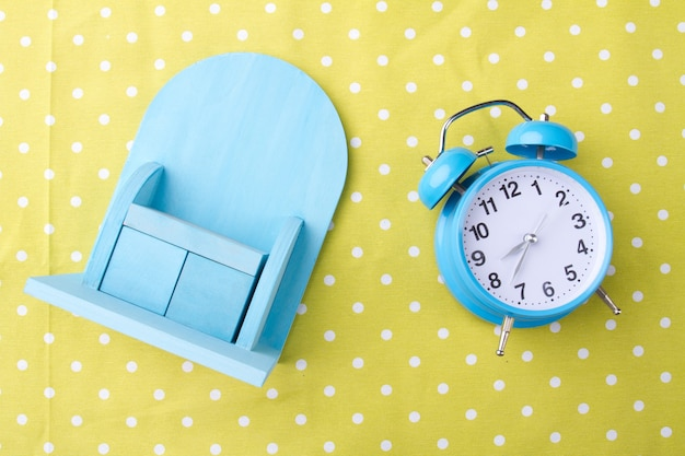 Miniaturschrank und wecker auf gelbem hintergrundmorgenzeitkonzept flachfoto