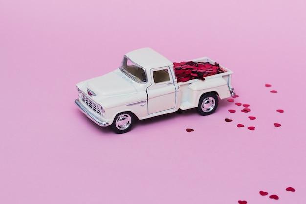 Miniaturspielzeugauto, das rote herzkonfetti für valentinstag auf rosa hintergrund liefert