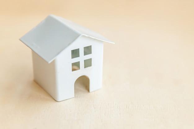 Miniaturspielzeugmodellhaus auf hölzernem hintergrund. eco village abstrakter umwelthintergrund