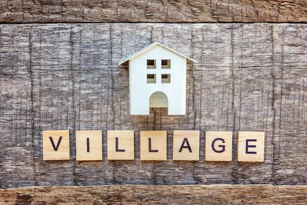 Miniaturspielzeugmusterhaus mit aufschrift dorf beschriftet wort auf holztisch