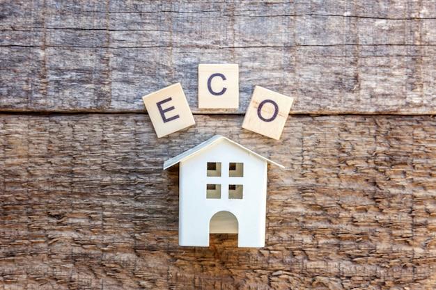 Miniaturspielzeugmusterhaus mit aufschrift eco beschriftet wort auf holztisch