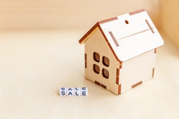 Miniaturspielzeugmusterhaus mit aufschrift verkauf beschriftet wort.