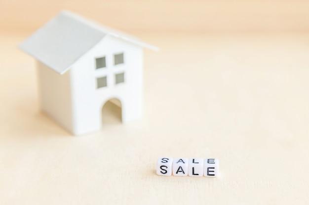 Miniaturspielzeugmusterhaus mit aufschrift verkaufs-buchstaben. eco village, abstrakter klimahintergrund. süßes hauptökologiemietenkonzept der immobilienhypotheken-sachversicherung
