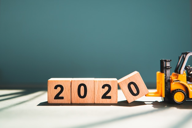 Miniaturstapler heben holzblock jahr 2020 unter verwendung als geschäfts- und industriekonzept