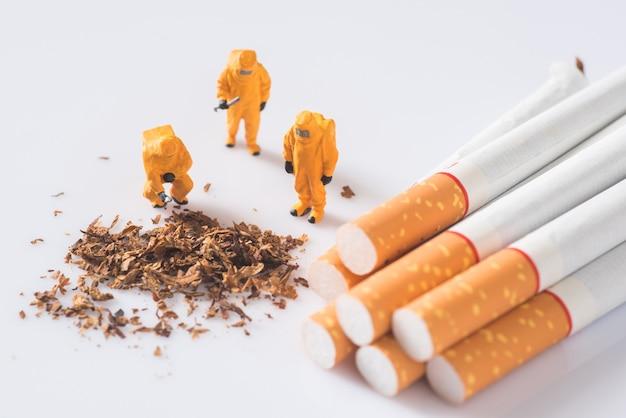Miniaturtechniker, der verunreinigungen in der zigarette überprüft