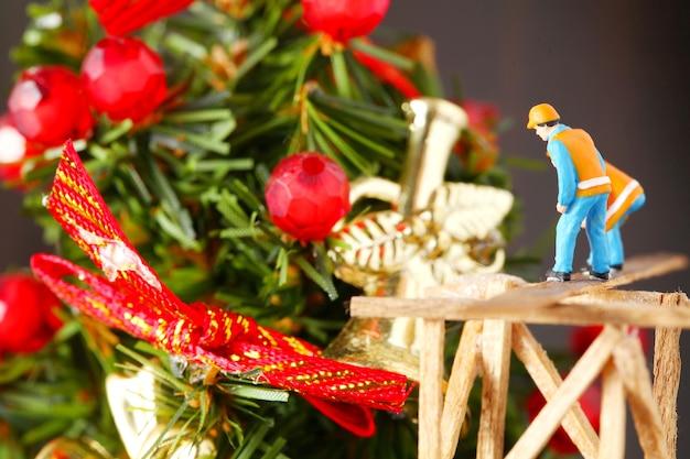 Miniaturwartungsplastikzahlmodell in der aktion des kleinen weihnachtsbaums der inspektion