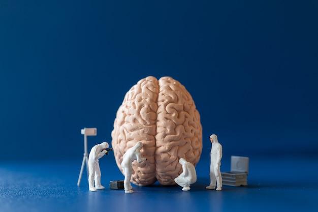 Miniaturwissenschaftler, der ein großes menschliches gehirn auf blauem hintergrund beobachtet und repariert
