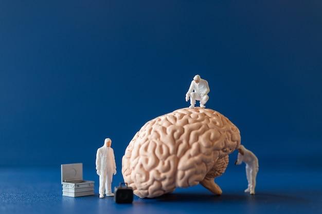 Miniaturwissenschaftler, der ein großes menschliches gehirn auf blauem hintergrund beobachtet