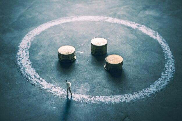 Miniaturzahl geschäftsmänner, die um die außenseite des kreidekreises mit münze gehen.