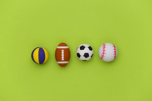 Minibälle verschiedener sportarten auf grünem hintergrund. minimalismus sportkonzept. ansicht von oben. flach liegen.