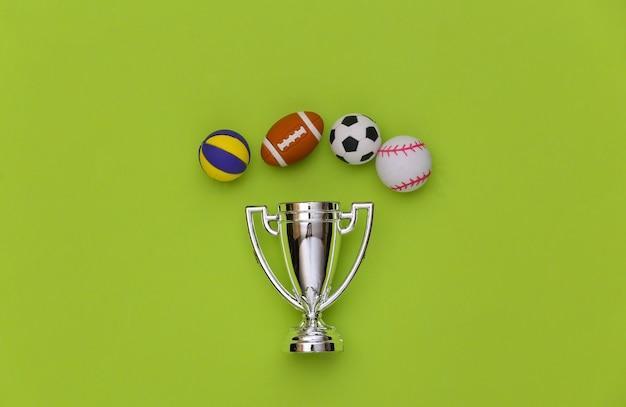 Minibälle verschiedener sportarten und meisterpokal auf grünem hintergrund. minimalismus sportkonzept. ansicht von oben. flach liegen.