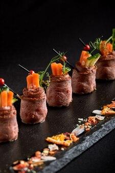 Minibratenrindfleisch rollt mit gemüse, auf einer schwarzen schieferplatte, auf einem schwarzen hintergrund. fusionslebensmittelkonzept, zurückhaltend, kopienraum.