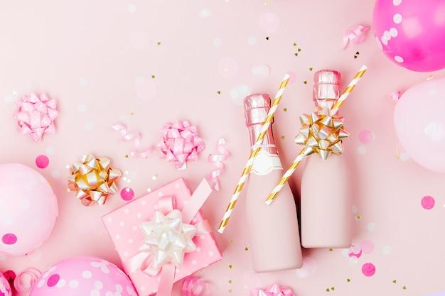 Miniflaschen champagner mit konfetti und lametta auf blassrosa hintergrund. valentinstag oder geburtstagsfeier-konzeptthema. flache lage, ansicht von oben