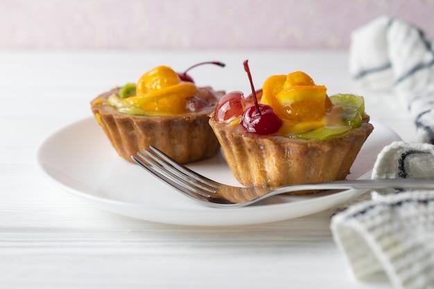 Minifruchttörtchen mit orange kirsche und kiwi auf weißer platte.