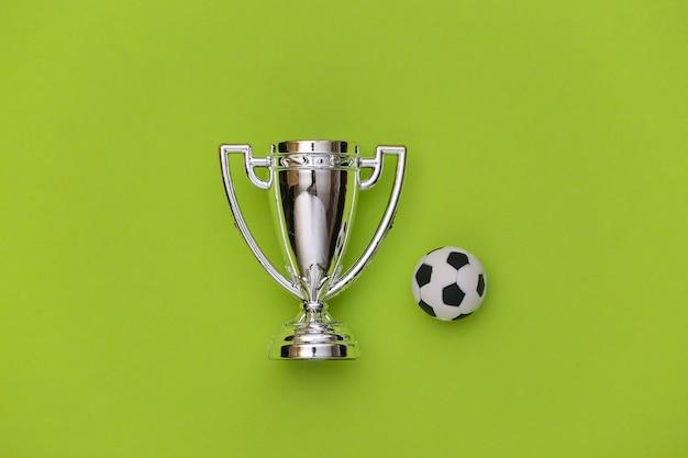 Minifußball und meisterpokal auf grünem hintergrund. minimalismus sportkonzept. ansicht von oben. flach legen