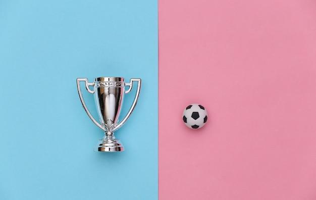 Minifußball und meisterschale auf einem blauen rosa pastellhintergrund. minimalismus sportkonzept. ansicht von oben. flach legen