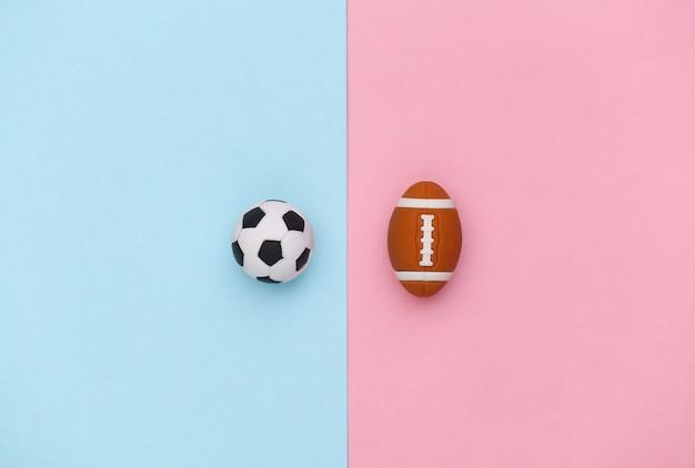 Minifußball und rugbyball auf einem blau-rosa pastellhintergrund. minimalismus sportkonzept. ansicht von oben. flach legen