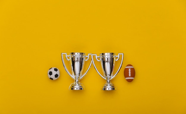 Minifußball und rugbyball, meisterschaftspokale auf gelbem hintergrund. minimalismus sportkonzept. ansicht von oben. flach legen