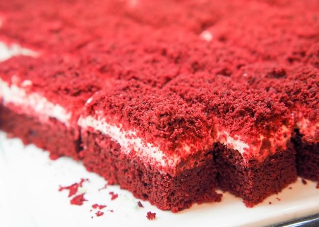 Minigröße des roten samtkuchens ordnete auf einer weißen platte an. schließen sie oben vom roten samtschokoladenkuchen für mahlzeitbuffet- oder -bankettereignisse.